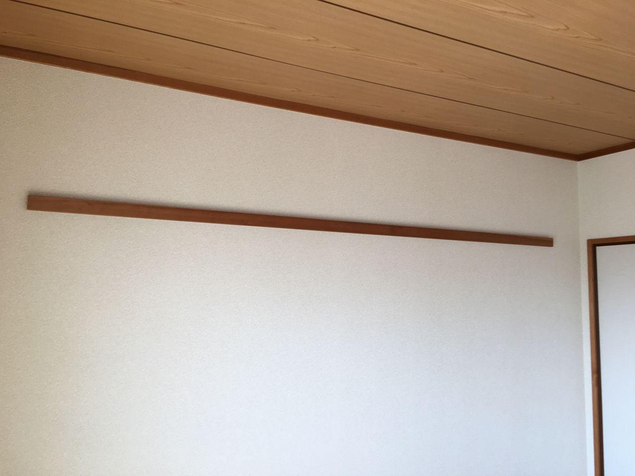 洋服かけ用の木製バーのある和室