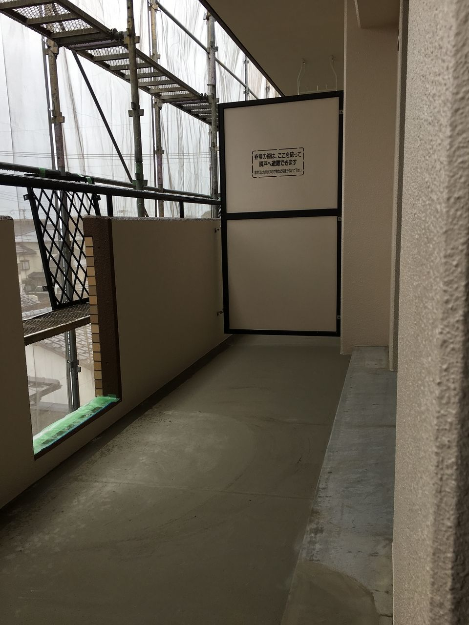 部屋側から見た足場と養生ネットです。バルコニーの床にも防水の下地が施してあります。